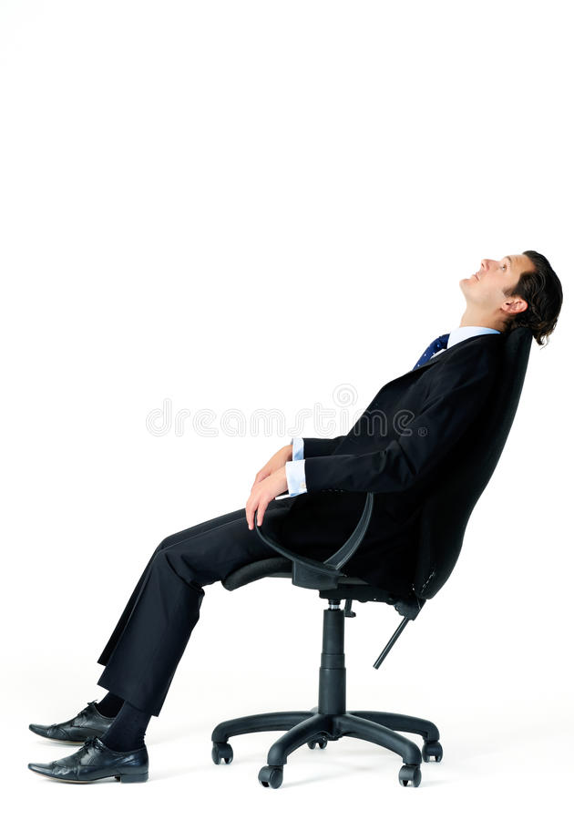 Distracted man in suit. Corporate worker in business suit leans back on his office chair, daydreaming about his upcoming vacation stock photo
