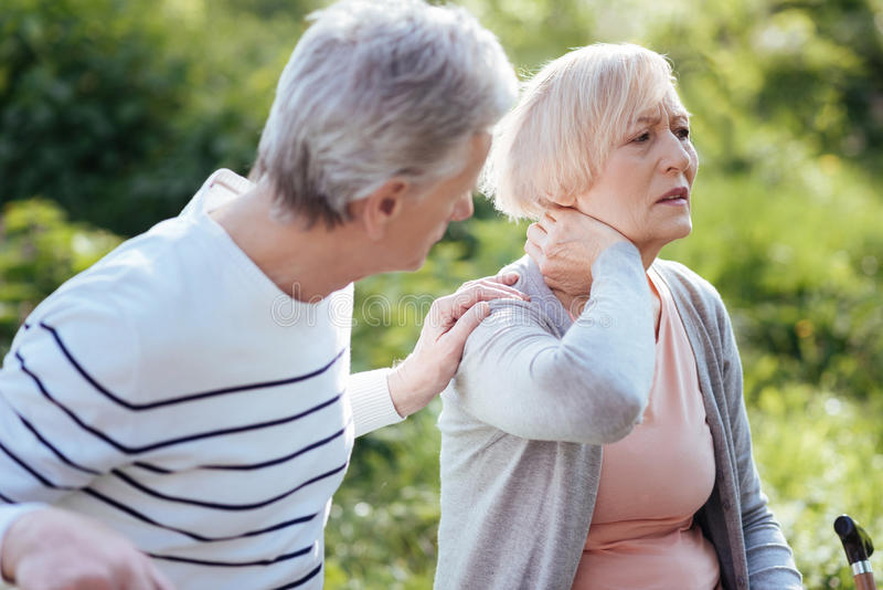 Distracted pensioner feeling terrible pain in the neck outdoors. It hurts me so much. Retired sad disturbed women touching her neck and feeling pain while her royalty free stock photos