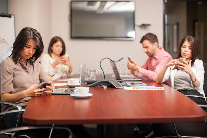 Distracted by technology. Group of people sitting in a meeting room and being distracted by their smartphones stock image