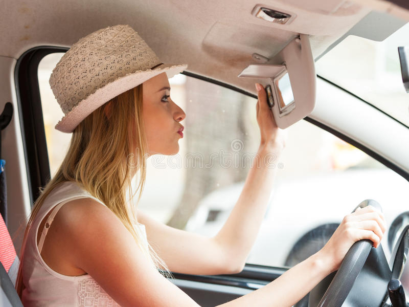 Distracted woman driving her car looking in mirror. Distracted driver. Young attractive woman looking in mirror while driving the car stock image