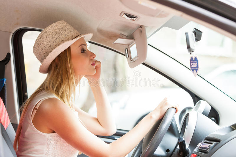 Distracted woman driving her car looking in mirror. Distracted driver. Young attractive woman looking in mirror while driving the car royalty free stock photography