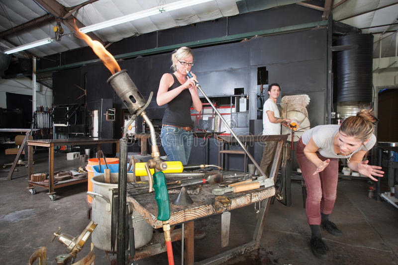 Distracted Glass Workers. Distracted worker looking at co-worker from behind in glass factory stock photos