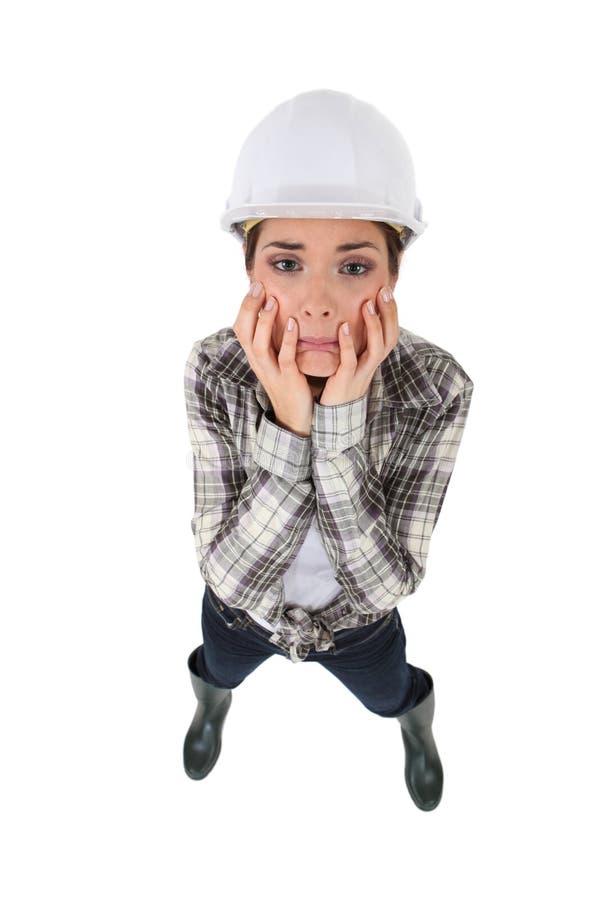 Distraught kvinnligbyggnadsarbetare royaltyfria bilder