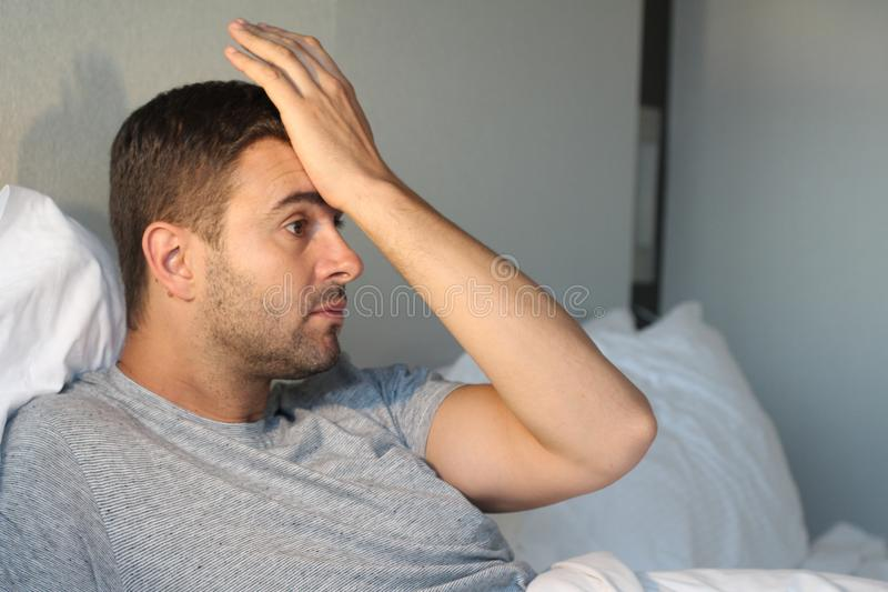 Distraught man with hand in forehead stock photos