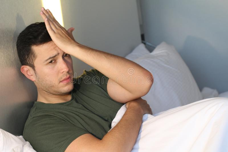 Distraught man with hand in forehead stock images
