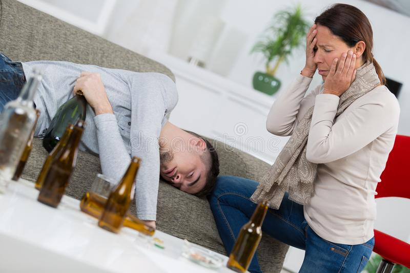 Distraught mother finding son passed out from alcohol. Alcohol stock photography