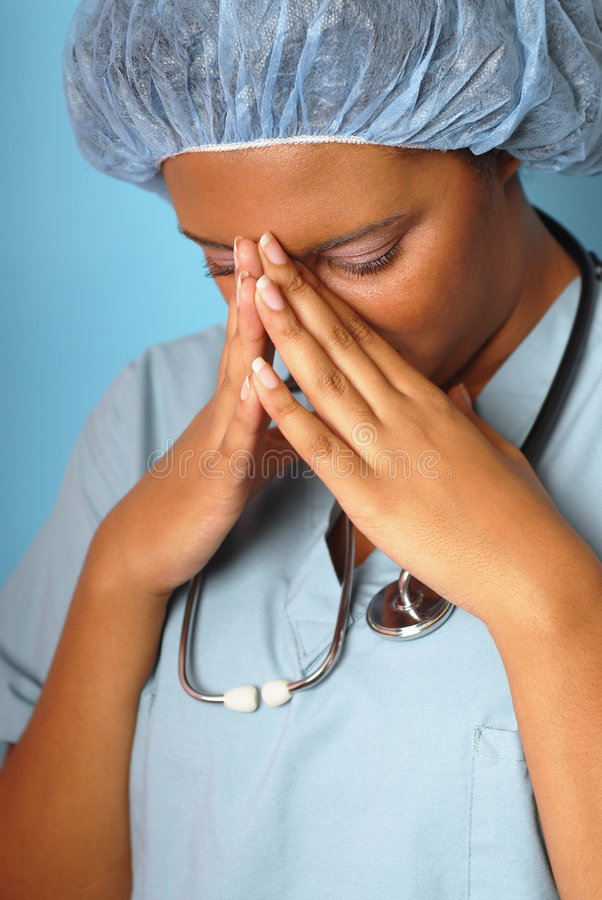 Distraught nurse. Crying nurse with her hands on her face royalty free stock photo