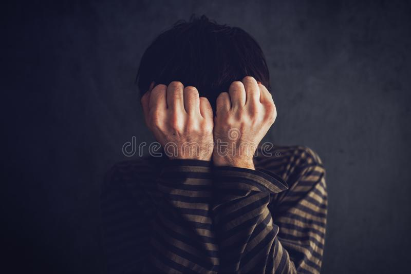 Distraught state of mind. Depressive and sad man in dark room stock images