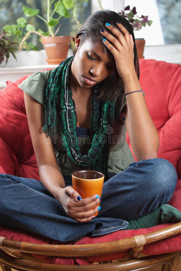 Distraught woman sitting on chair stock images