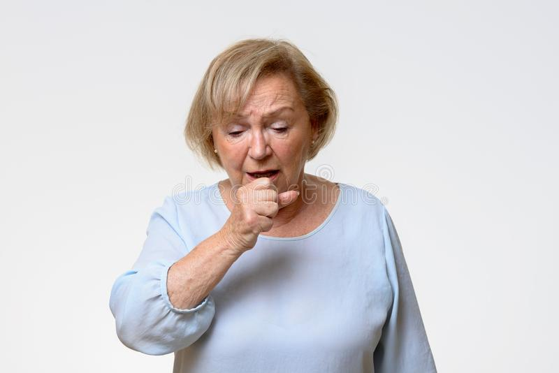 Distressed senior woman coughing. Holding her hand politely in front of her mouth in a front view on grey with copy space stock photos