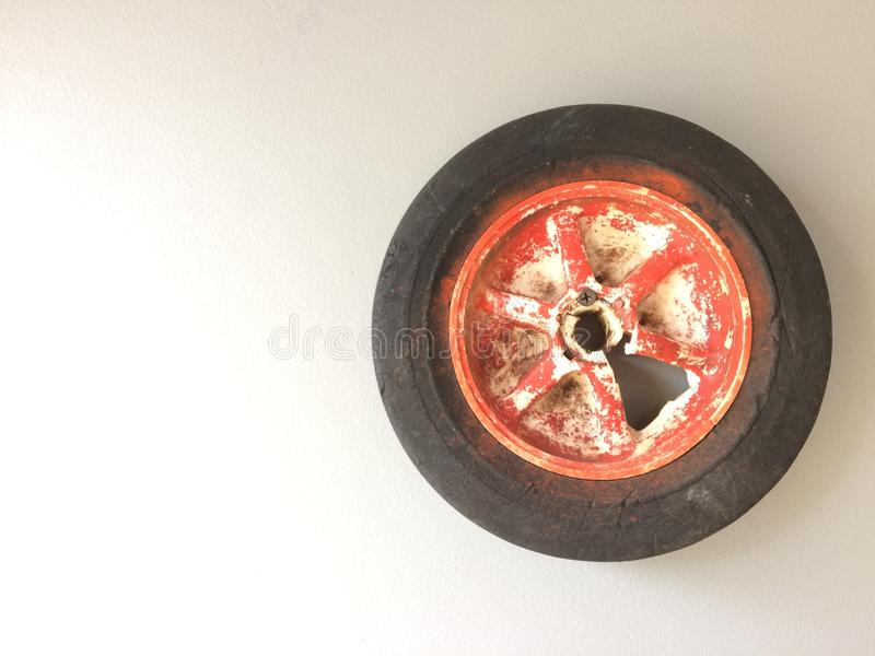 Distressed wheel old tire with red peeled paint spokes round grunge gritty shabby. Old bike tire broken wheel found object red and white peeled paint rubber stock photo
