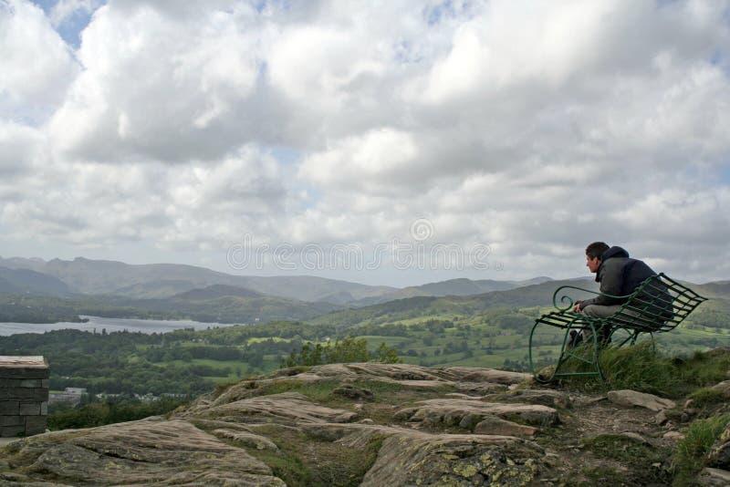 Distretto del lago, Regno Unito - aprile 2011: Uomo sul banco della sommità fotografia stock