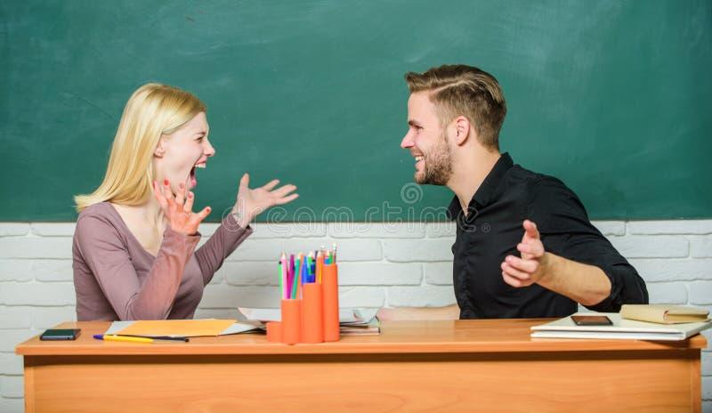 Distribuci?n de buenas noticias Pares felices que estudian en sala de clase Profesor y profesor que se sientan en el escritorio H imagenes de archivo