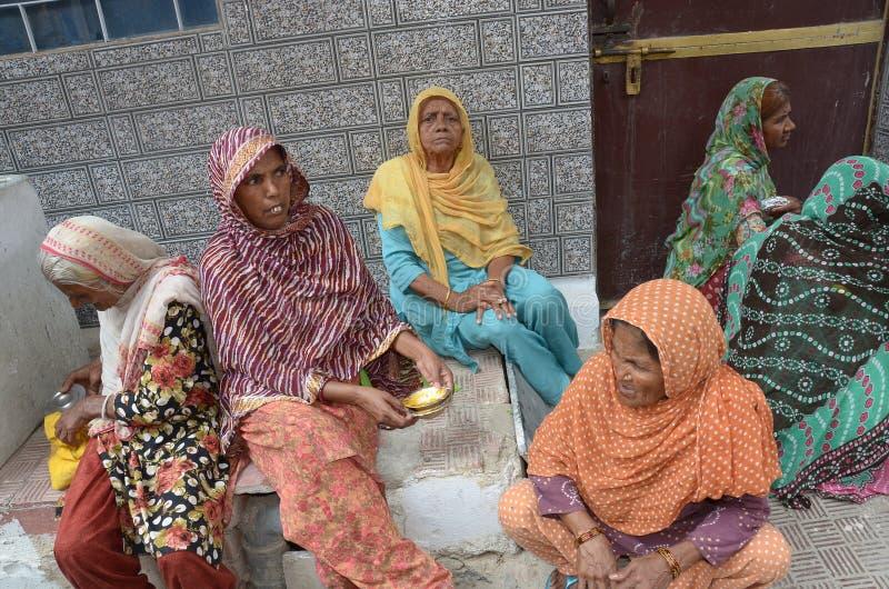 Distribuez la nourriture pour les pauvres femmes photo libre de droits