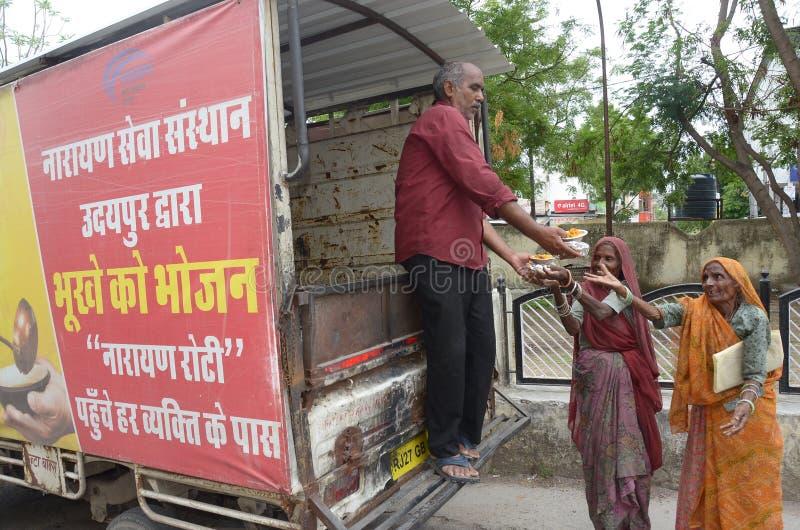 Distribuez la nourriture pour les pauvres femmes par Narayan Seva Sansthan images stock