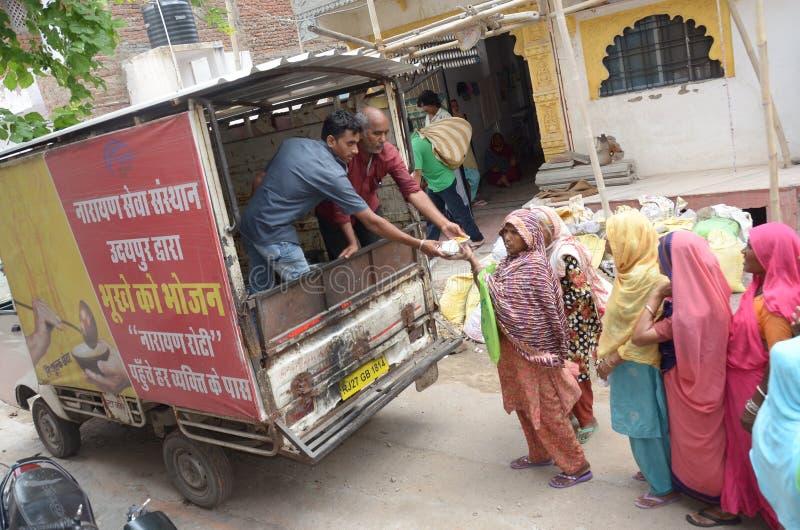 Distribuez la nourriture pour les pauvres femmes par Narayan Seva Sansthan photos stock