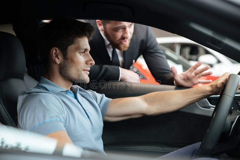 Distribuidor autorizado de sexo masculino profesional que vende el coche a un cliente fotos de archivo