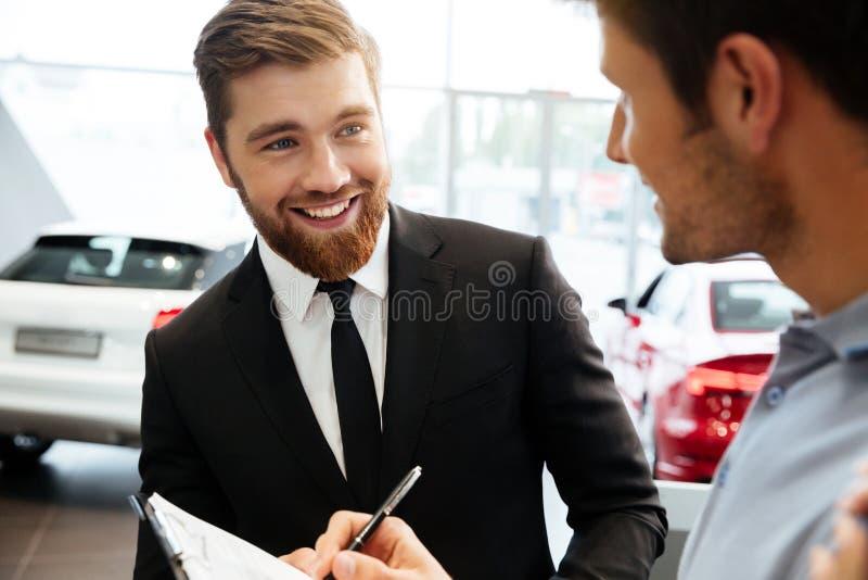 Distribuidor autorizado joven sonriente que vende el nuevo coche a un cliente masculino foto de archivo