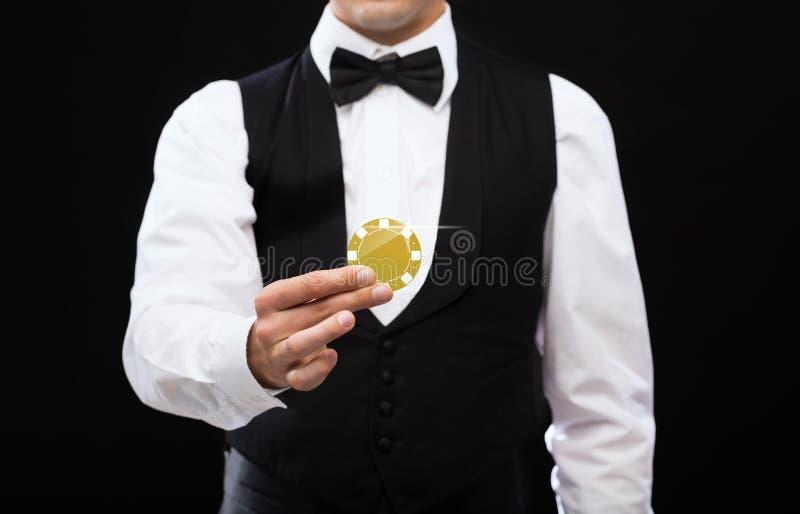 Distribuidor autorizado que sostiene la ficha de póker de oro imagen de archivo libre de regalías