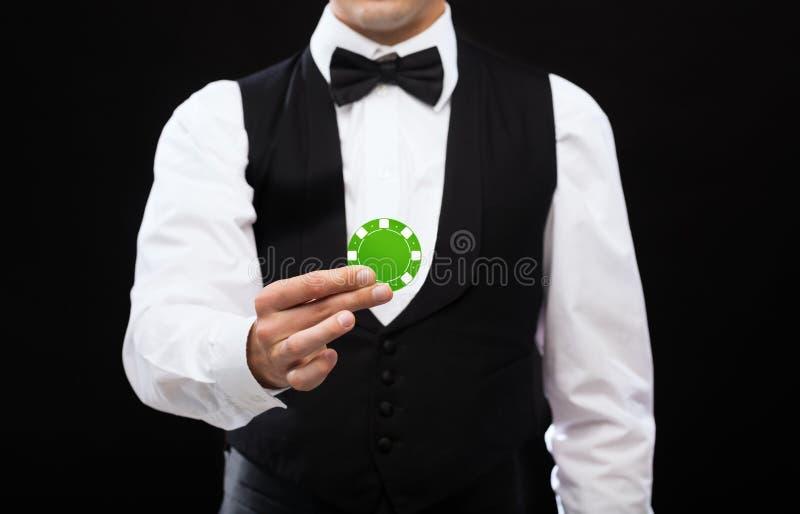Distribuidor autorizado que sostiene la ficha de póker verde foto de archivo libre de regalías