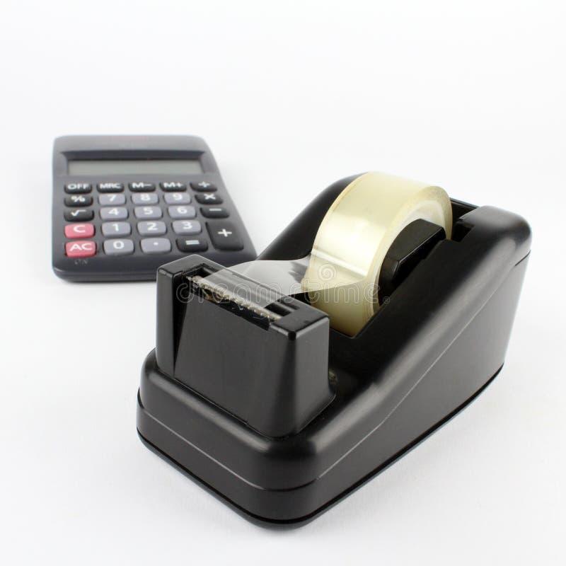 Distribuidor da fita da mesa com calculadora fotografia de stock