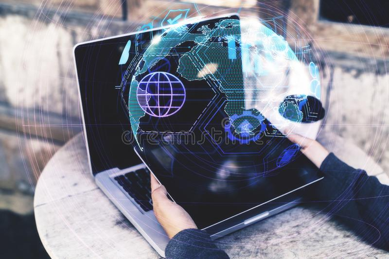 Distributed data and internet concept. Close up and side view of hands using laptop with digital globe interface on blurry background. Distributed data and stock photos