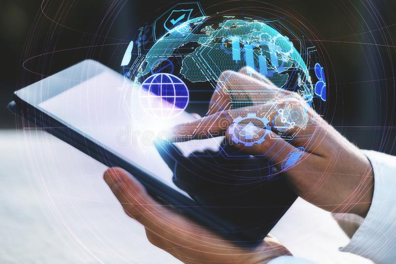Distributed data and network concept. Close up and side view of hands using tablet with digital globe interface on blurry background. Distributed data and royalty free stock image