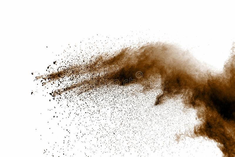 Distributed powder. Explosion of brown dust on white background stock photo