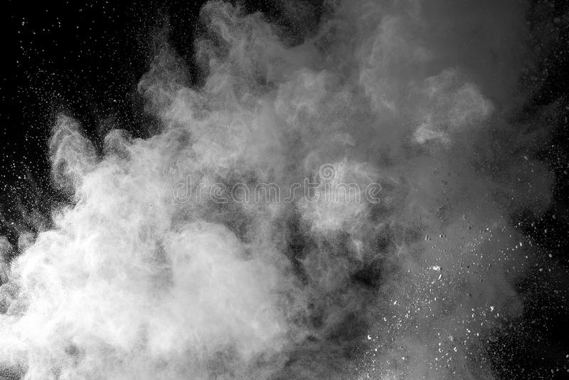Distributed powder. Explosion of white dust on black background stock photography
