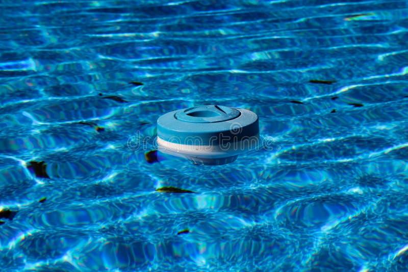 Distributeur bleu lumineux clair comme de l'eau de roche de chlore flottant dans une piscine photographie stock