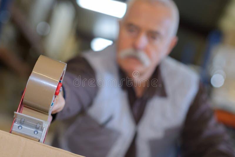 Distributeur de bande de plan rapproché employé par l'homme supérieur photographie stock