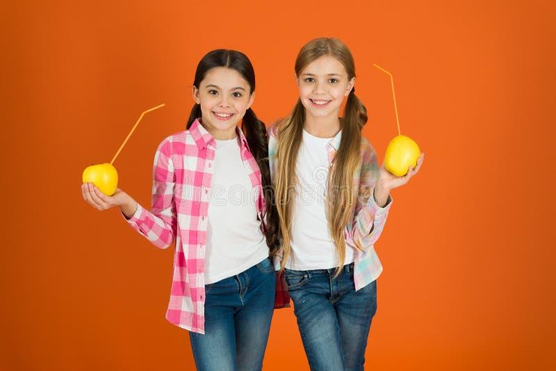 Distributing free fresh fruit at school. Girls kids casual style eat apple fruit orange background. Schoolgirls eat. Apple fruit. School lunch. Vitamin fruit stock image