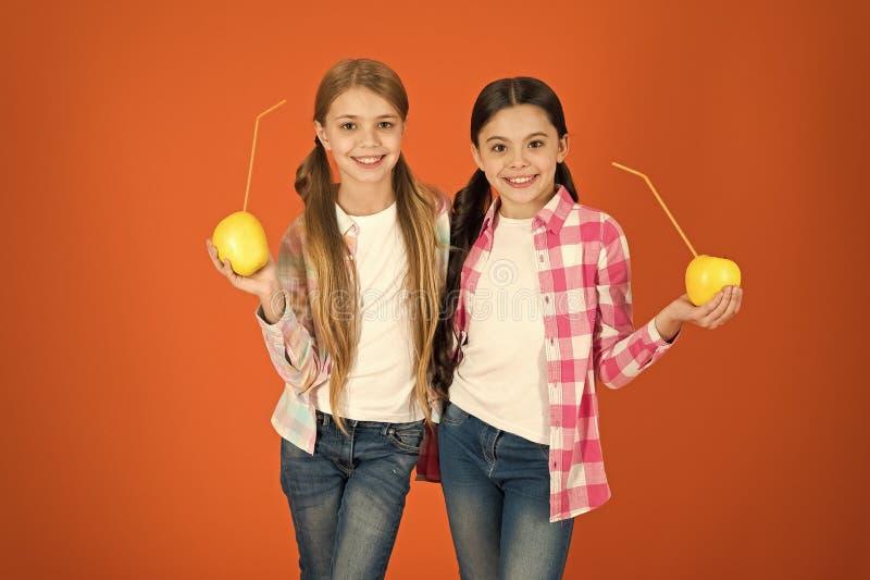 Distributing free fresh fruit at school. Girls kids casual style eat apple fruit orange background. Schoolgirls eat. Apple fruit. School lunch. Vitamin fruit royalty free stock images