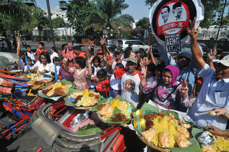 Distribution of free food to the poor people. Supporters of Indonesian presidential candidate, Joko Widodo distribute free food to the poor people during a royalty free stock photography