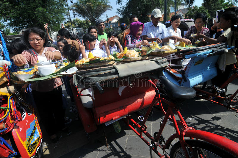 Distribution of free food to the poor people. Supporters of Indonesian presidential candidate, Joko Widodo distribute free food to the poor people during a stock photos