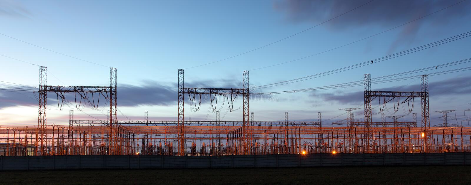 distribution substation silhouetted against dusk sky ,electricity background stock photography