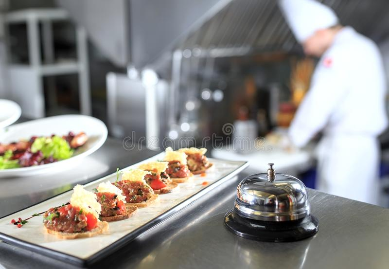 The distribution table in the kitchen of the restaurant. the chef prepares a meal on the background of the finished royalty free stock photography