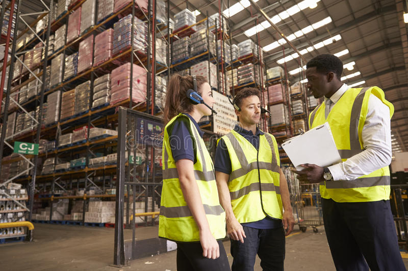 Distribution warehouse manager in discussion with colleagues stock photography