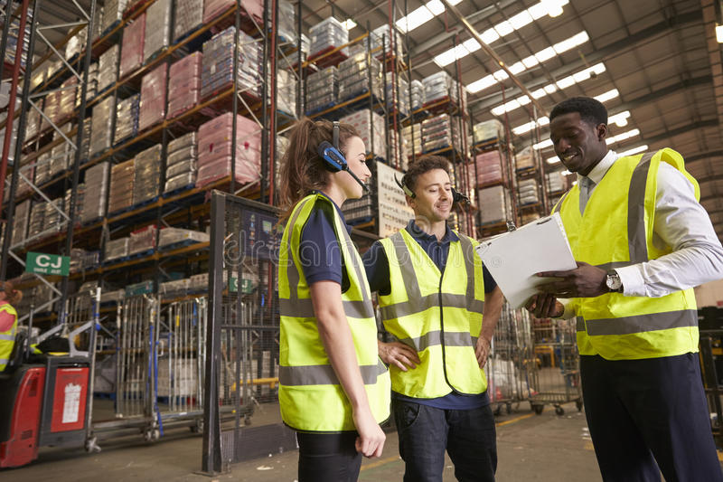 Distribution warehouse manager instructing colleagues stock image
