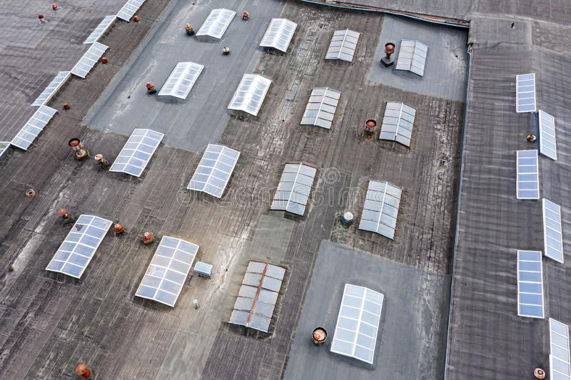 Distribution warehouse roof with skylights and ventilation systems from above. Distribution warehouse roof from above. ventilation systems are installed on the stock images