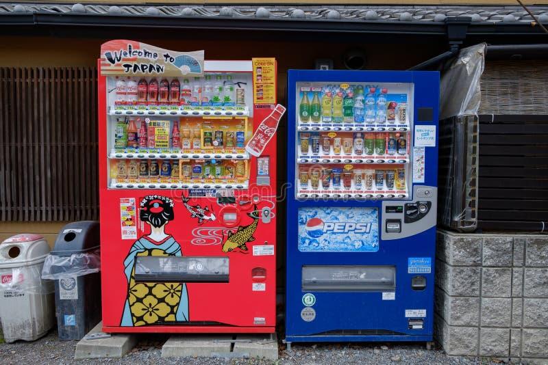 Distributori automatici di Pepsi e della coca-cola in pieno delle bevande fredde e calde nel concetto della concorrenza della via fotografia stock libera da diritti