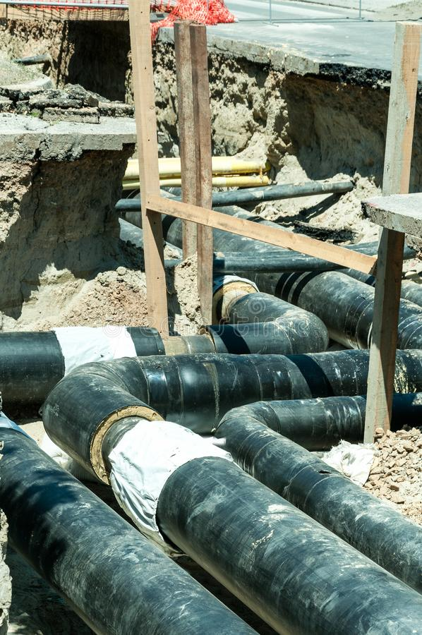 District heating pipeline reparation and reconstruction parallel with the street with construction site safety net fence. District heating pipeline reparation stock image