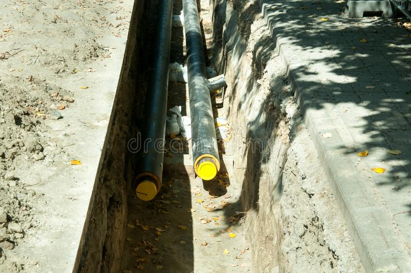 District heating pipeline reparation and reconstruction parallel with the street with construction site safety net fence. District heating pipeline reparation stock photography