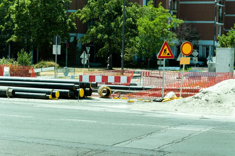 District heating pipeline reparation and reconstruction parallel with the street with construction site safety net fence. District heating pipeline reparation royalty free stock photography