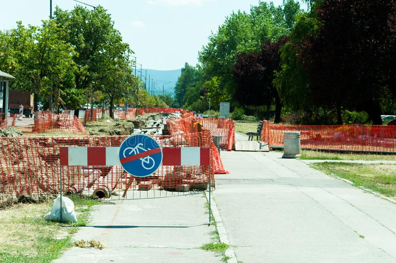 District heating pipeline reparation and reconstruction parallel with the street with construction site safety net fence. District heating pipeline reparation stock photos