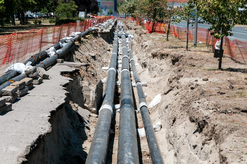 District heating pipeline reparation and reconstruction parallel with the street with construction site safety net fence. District heating pipeline reparation royalty free stock photos