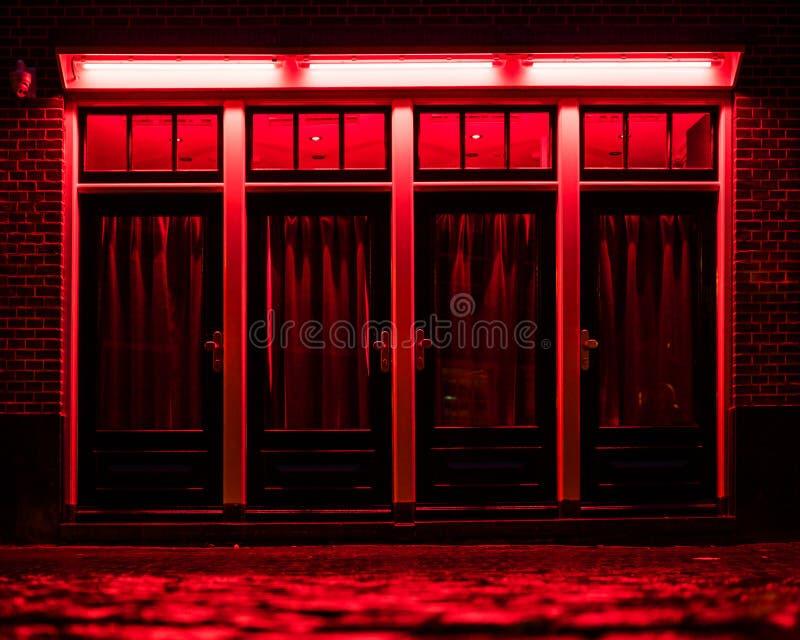 Districto de luz roja en Amsterdam Cajas rojas con las cortinas y los adoquines mojados en la calle foto de archivo