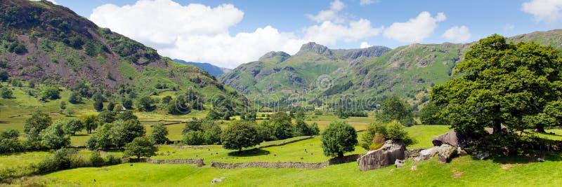 Distrito Cumbria do lago valley de Langdale com montanhas e panorama do céu azul imagem de stock