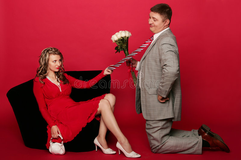 Distrust. Husband standing on his knee in front of wife with bouquet of roses and ask pardon royalty free stock photos