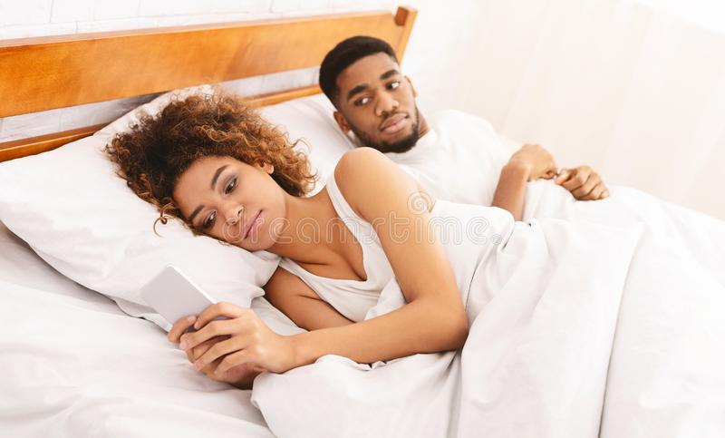 Woman chatting with lover on cellphone in bed stock photo